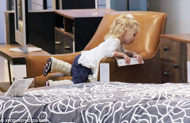 Playtime: The adorable two-year-old appeared to be taking the lead when it came to selecting suitable furniture for the family home