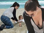 Life's a beach: Khloe and Kourtney Kardashian help bury delighted little Mason in sand during a family day out in Miami
