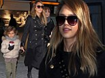 Battling the British weather: Jessica Alba and daughter Honor keep warm with hot beverages as they touch down in London