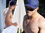 Shirtless Kellan Lutz shows off his impeccable physique as he relaxes poolside