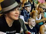 Finally... a smile! Madonna's stony face cracks as she's moved by a social music project in a Brazilian shanty town