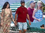 Hand-in-hand: Russell Simmons and his girlfriend Hana Nitsche take a romantic stroll down the beach in Miami on Thursday, and later bumped into Nicky Hilton