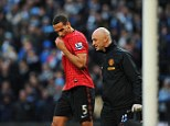 Wounded: Rio Ferdinand receives treatment from United's physio after being struck by an object thrown from the crowd following Robin Van Persie's late winner