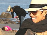 Time for my nap! Halle Berry's daughter Nahla gets playful as she lies down on the ground during windy beach stroll