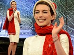 Jingle belle! Anne Hathaway shows her Christmas spirit as she slips on festive attire to sing her way through interview
