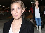 Low maintenance: A make-up free Kate Hudson carries her own luggage in to LAX