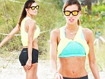 Why even bother with a top? Claudia Galanti bares her super toned midriff as she tucks her T-shirt into her crop top