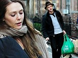 From boyfriend to bellboy: Elizabeth Olsen's loving beau Boyd Holbrook helps shift her bags as they exit hotel