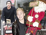 Getting ready for Christmas! Miley Cyrus takes home Santa... while fiance Liam Hemsworth stocks up at Whole Foods