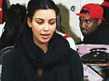 Kanye is seen sitting patiently in a nail bar as he waits for Kim to have her pre-Christmas pedicure.