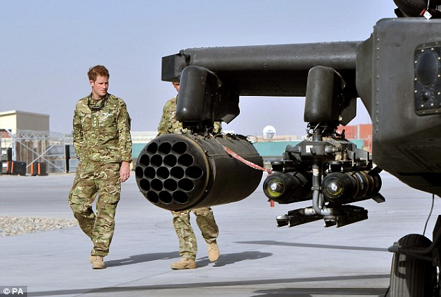 Powerful: Harry wanders past the weapons that he will be using tofight the Taliban