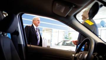 Dom Romeo, CEO of Pine View Pontiac Buick GMC Trucks, speaks with an employee in the showroom.