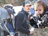 Good for their 'elf! Orlando Bloom utilises his Legolas cross terrain skills to carry son Flynn on a hike