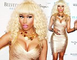 Taking the plunge! Nicki Minaj leaves little to the imagination in a VERY low cut gold dress for New Year's Eve party