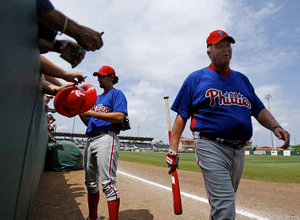 Charlie Manuel walks by as pitcher Gary Majewski signs autographs during spring training.