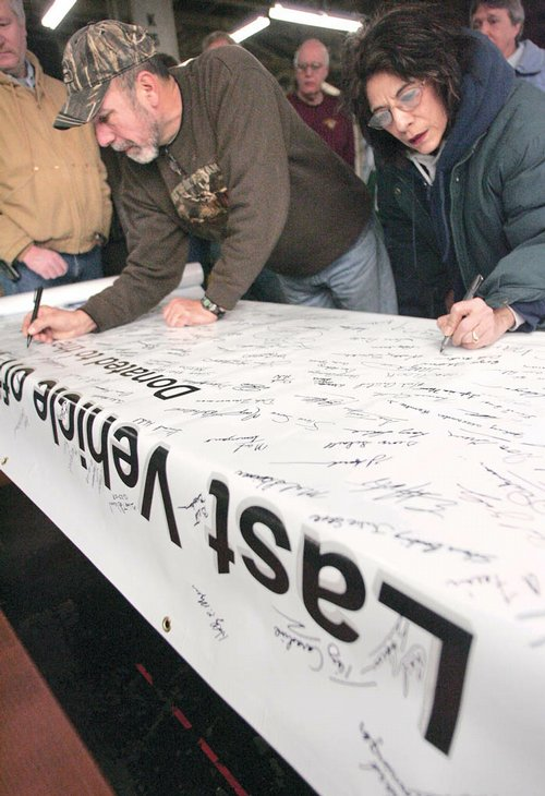 GM workers sign a banner comemmerating the last vehicle produced ...