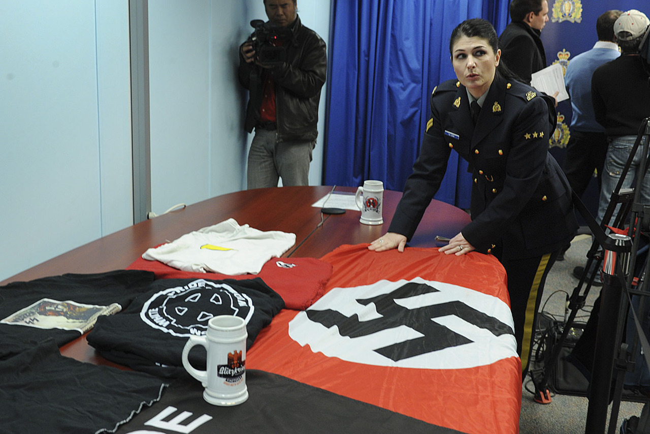"Normandie Levas, a Communist Jewess who works for the RCMP's division of enforcing Jewish Globalism, is pictured here at a press conference showcasing a few National Socialists flags and items. According to this evil whore of Zion, merely possessing flags or coffee mugs with a Swastika on it is a ""hate crime"", but communist flags and posters of Stalin and Lenin is somehow not considered hateful or ""extreme"" in any way. The Jew World Order are trying to ""sex up"" the enforcers of their iron rule, recruiting women to fill the role of tyrannical police commissar like this disgusting witch."