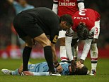 Flat out: Daniel Potts was knocked unconcious following a clash of heads with Arsenal defender Bacary Sagna