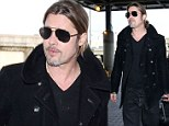 'We have a very normal, very grounded home': Brad Pitt takes solo flight at LAX...as Angelina Jolie opens up about their family