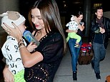 Orlando Broom and Miranda Kerr play the perfect parents as they arrive at Los Angeles International Airport with son Flynn on Saturday