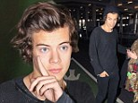 Hat hair Harry! Styles' famous mane looks less than sleek as he jets back to London