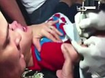 Sickening: A mother holds down her toddler son as he screams in agony while being given a tattoo