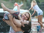 Are you looking, LeAnn? Brandi Glanville revels in playing with HER boys while she washes the car (showing off her great pins)