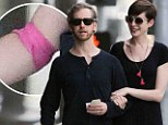 Expecting more than an Oscar? Anne Hathaway sports bandage after leaving medical center with her husband