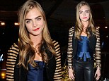 cuts a chic figure in peplum top and leather trousers at exclusive Burberry show