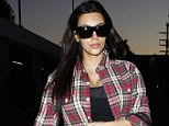 Check mate: Determined Kim Kardashian headed to the gym at the crack of dawn on Wednesday morning sporting the same checked shirt as the previous day, teamed with black workout pants and a plunging vest top