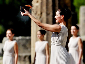 Actress Maria Nafpliotou, who is playing the role of an ancient Greek priestess, holds a pot with the Olympic Flame (AFP Photo / Aris Messinis)