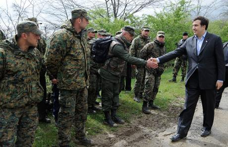 Georgian President Mikhail Saakashvili, right, shakes hands with soldiers who took part in a mutiny