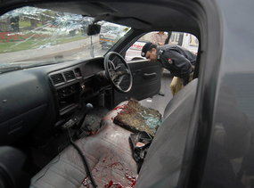 A policemen inspects a police car covered in blood after the attack.