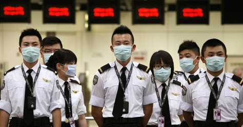 Contract staff of Port Health stand in attention before shifting duties at the Hong Kong Airport Thursday, April 30, 2009. (AP / Bobby Yip)