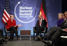 U.S. President Barack Obama (C) and German Chancellor Angela Merkel sit together during their bilateral meeting as U.S. Secretary of State Hillary Clinton looks on at the Nuclear Security Summit in Washington April 13, 2010.