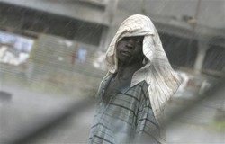 A Southern Sudanese man covers his head under heavy rains in Juba, South Sudan, Tuesday, April 13, 2010 during the third day of the elections which were billed as a chance to bring democracy to Sudan and start to heal a history of turmoil. The elections ending Thursday are expected to keep President Omar al-Bashir in power for another five years, even though he is under an international indictment for alleged war crimes in Sudan's Darfur region.