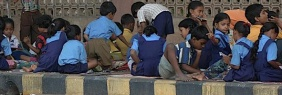 Students from a street school attend their class on the pavement in Mumbai May 9, 2007. REUTERS/Sima Dubey/Files