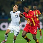 Asamoah Gyan of Ghana challenges Jonathan Bornstein of the United States