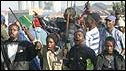 South Africans holding sticks and knives shout anti-foreigner slogans as they riot in the Reiger Park informal settlement outside Johannesburg, 19 May