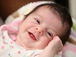 Bundle of joy: Baby Chloe smiles a week after she was found dumped in a plastic bag in Houston