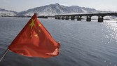 A Chinese flag is hoisted near the Hekou Bridge, right, linking China and North Korea