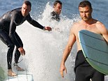 Surf's up! Liev Schreiber shows impressive skill as he rides a wave... before wiping out