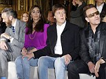 Taking it all in: Sir Paul placed a protective hand on his wife's knee as they took in the show