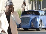Calling AAA? Serious looking will.i.am makes phone call as he stands beside his $900,000 custom car