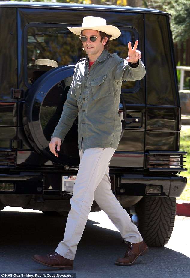 Smooth operator: Bradley flashed the peace sign while sporting his clean-shaven look on Friday