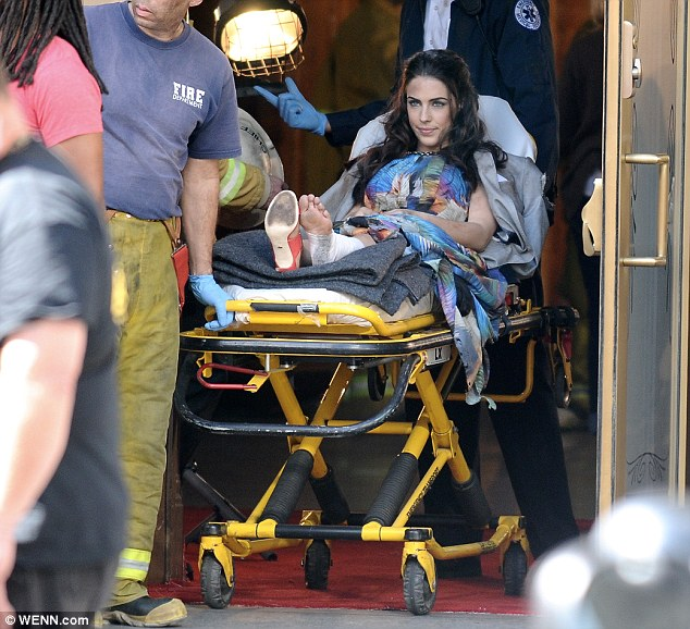 That's not good: Jessica Lowndes is seen being pulled on in a stretcher