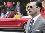 Hamm wore a pair of gold rimmed spectacles and a sharp grey suit as he took a spin in a vintage 1965 Ford Mustang.