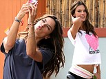 The camera loves her! Alessandra Ambrosio snaps photos on her phone as she models workout wear for Victoria's Secret