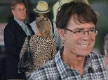 Cliff Richard looks happy as he waits at Barbados airport with companion John McElynn on Wednesday