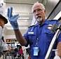 TSA officer Robert Howard signals an airline passenger forward at a security check-point